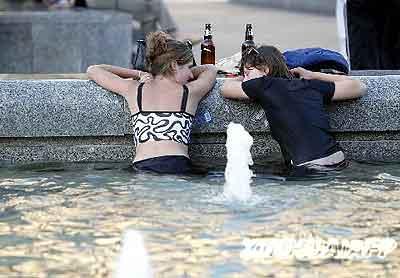 乌克兰少女在喷水池中享用啤酒 躲避暑热