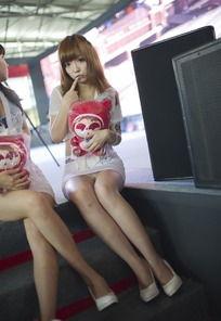 游戏展坐在舞台楼梯上的大露背超短裙性感女郎