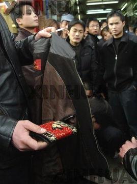 衣民警在展示小偷偷的钱包.当日,在该市人民路巢州影剧院附近,两...