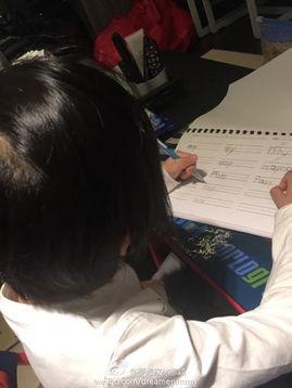 imi左手拿笔趴在桌子上写作业.有网友大赞kimi可爱,也有网友注意到...