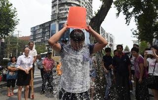 ...起水桶.摄影:南飞-武汉街头上演 冰桶挑战赛 美女湿身
